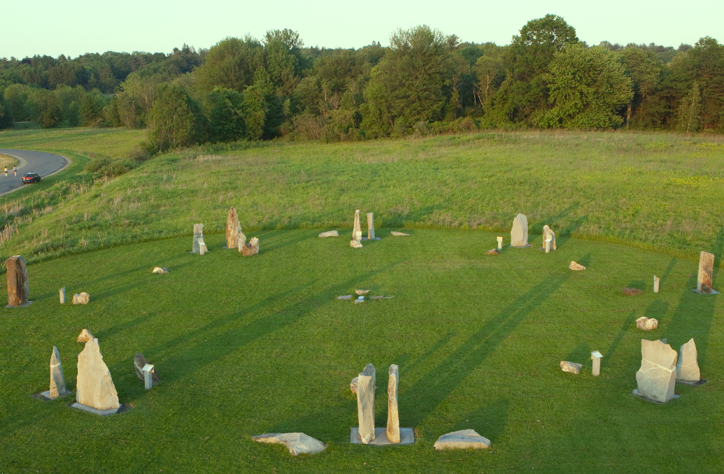 aerial view of sunwheel during summer solstice, in green field surrounded by meadow and trees