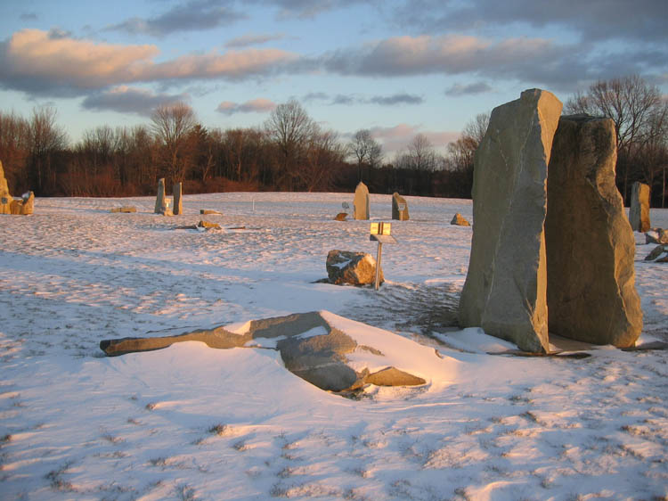 Photo of snowy field surrounded by bare trees. A series of rock pillars about twice the size of a person are arranged in a circle . The sun is setting and casting shadows across the snow.
