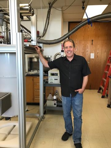 Grant Wilson standing next to equipment in lab