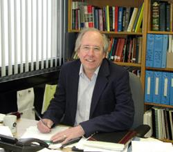 Photo of Ron Snell at desk in front of bookshelf