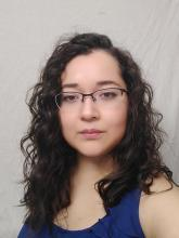 headshot-style phot of a woman with medium length curly brown hair and light skin, wearing a blue shirt and glasses,