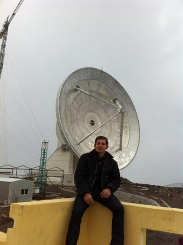 Kamal Souccar wearing a jacket, sitting on a corner wall in front of telescope