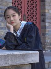 Person wearing graduation robe with arms resting on concrete wall, standing in front of a brick wall witha red lattice door