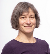 Portrait of smiling woman with short grey hair and purple shirt