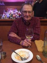 Picture of Bill Irvine at a restaurant table with plate and glass of wine
